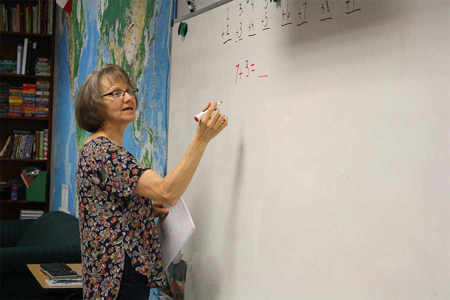 Teacher Margo Haughee stand in front of a whiteboard in her classroom